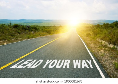Lead your way, concept photo of asphalt road. Motivational inscription on the road going forward. The beginning of a new path. A conceptual photo of the path.