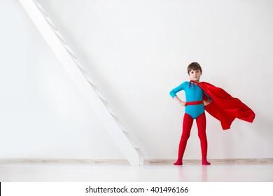 Leader. The boy super hero in a red cloak in the wind.