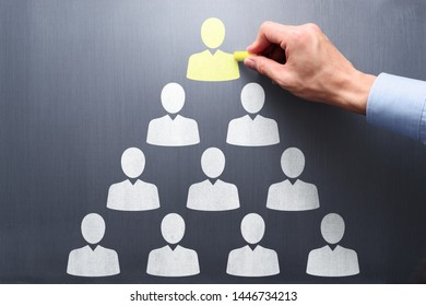 Leader of company organization. Human resource management and leadership concept. Businessman drawing pyramid structure on chalkboard.