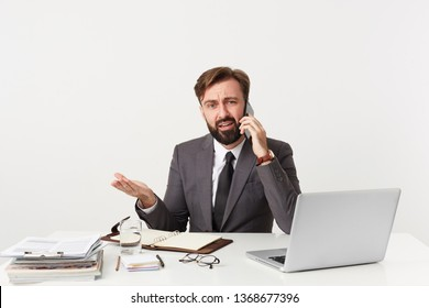 Leader of the company sitting at desktop in office, has unpleasant telephone conversation, he is told absurd things, argues with someone, is good looking, dressed in a suit with a tie, has beard