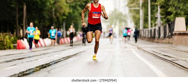 leader marathon race athlete runner run in rain on city street