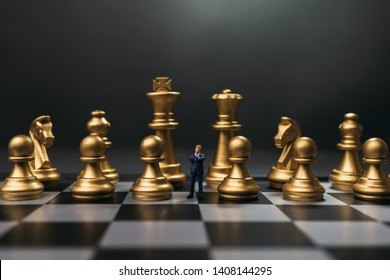 Leader miniture in the midst of gold chess on chessboard with low light.