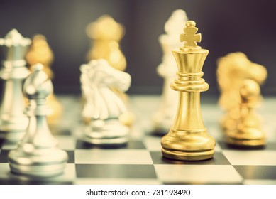 Leader or winner / commander concept : Side view of a golden king chess piece with silver knight and others, align on black white 8 x 8 grid chessboard. Chess is a 2 players strategy board game.