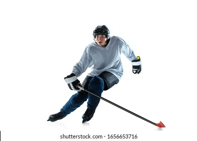 Leader. Young male hockey player with the stick on ice court and white background. Sportsman wearing equipment and helmet practicing. Concept of sport, healthy lifestyle, motion, movement, action.