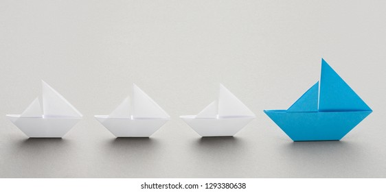 Leadership. Big blue paper boat leading small white ships, going to aim, panorama, copy space