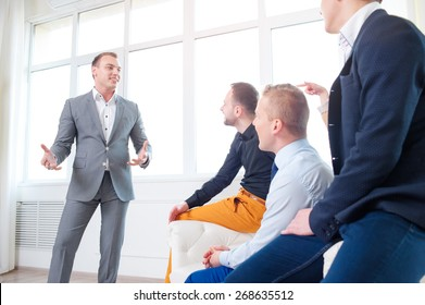 Leadership and charisma. Business speech. Handsome young man in grey suit talking to his colleagues - group of young people.