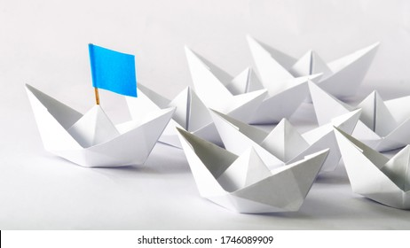 Leadership concept. Blue flag Origami White Paper boat (ship) leading the others.  One leader ship leads other ships.