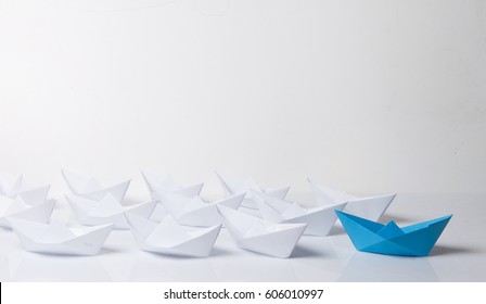 Leadership concept. Blue paper boat leading among white ships. Set of origami boats. Winner red paper ship on white background