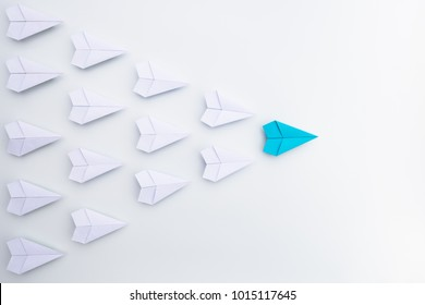 Leadership concept with blue paper plane leading among white.