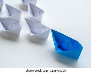 Leadership concept. Blue paper ship lead among white. One leader ship leads other ships.
