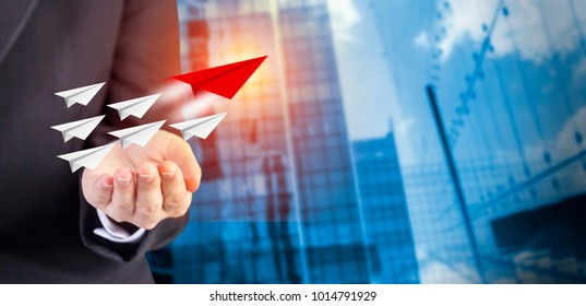 Leadership concept of business woman hand with paper planes on modern building in the city with sunlight