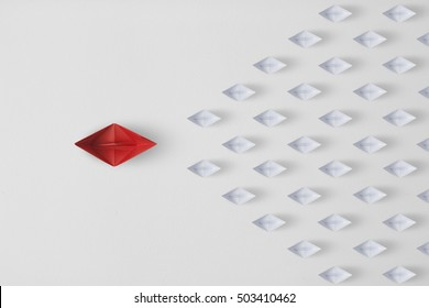 Leadership concept minimal  with red paper ship leading among paper ship white.