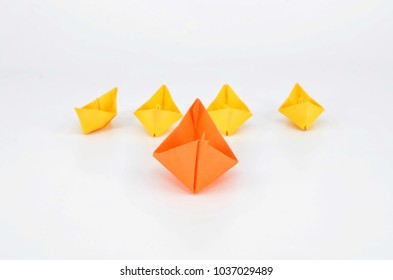 Leadership concept with a orange paper ship leading among yelllow ships
