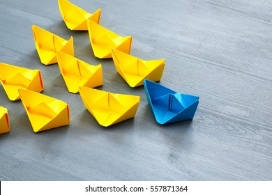 Leadership concept with paper boats on blue wooden background. One leader ship leads other ships. Filtered and toned image
