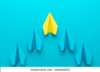Leadership concept with paper planes over turquoise blue background with copy space. Top view of yellow plane leading blue ones. Flat lay image of business competition concept.