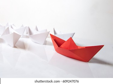 Leadership concept. Red paper boat leading among white ships on white background. Set of origami boats. Winner red paper ship on white background.
