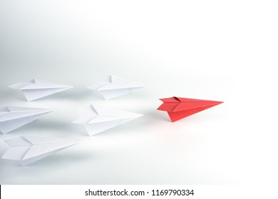 Leadership concept with red paper plane leading among white.