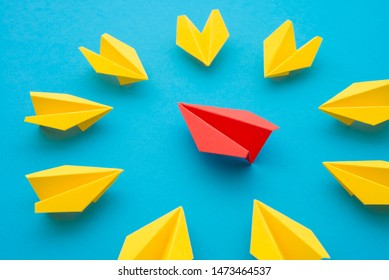 Leadership concept. Red paper plane origami leading among small yellow planes on blue background. Leadership skills need for top management in organization, company such as supervisor, manager, CEO