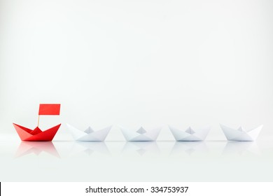 Leadership concept with red paper ship leading among white