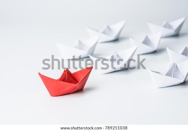 Führungskonzept mit rotem Papierschiff, das unter weiß führt