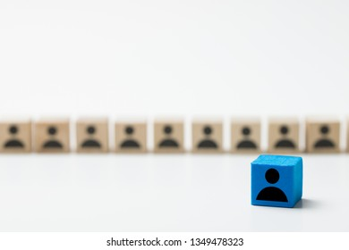 Leadership concept using blue people icon cube among many other cubes