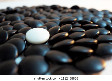 Leadership concept, white circle stone leading blacks Business concept as a group of white circle stone  in one direction and with one individual pointing in the different way as a business icon
