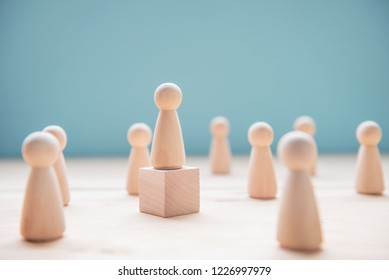 Leadership concept. Wood person model among people on blue background.