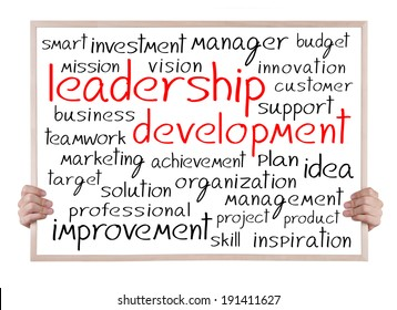 leadership development and other related words handwritten on whiteboard with hands