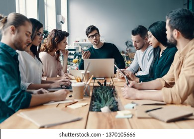 Leadership. Group of young modern people in smart casual wear discussing something while working in the creative office