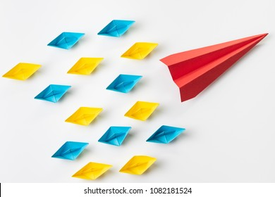Leadership, influencer, KOL, key opinion leader concept, big red paper plane origami fly lead in front of colorful small yellow and blue paper ship fleet on white background.