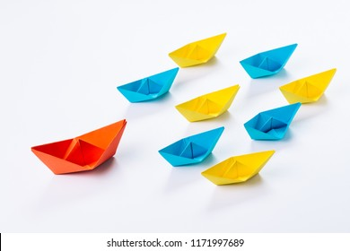 Leadership, influencer, KOL, key opinion leader new marketing channel concept, big red paper ship origami lead in front of others small yellow and blue fleet on white background.