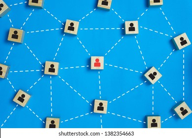 Leadership and network teamwork concepts Red businessman icon on the wooden block in the middle between the black business icon on the wooden blocks. Depicts network and work that is a perfect team.