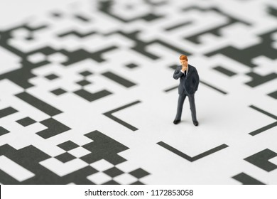 Leadership, solution for business idea concept, miniature figurine businessman standing at the center of confusing QR code labyrinth maze thinking to be success with confident.