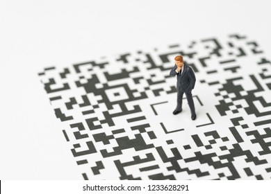 Leadership, solution for digital business idea concept, miniature figurine businessman standing at the center of confusing QR code labyrinth maze thinking to be success with confident.