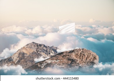 Leadership and success concept with blank white flag on mountain top. Mock up