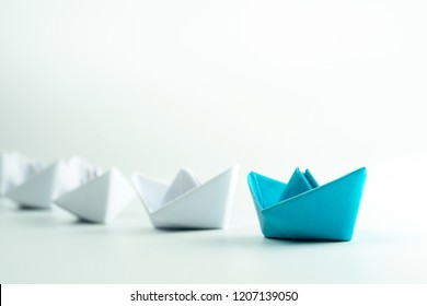 Leadership and Success concept with Blue paper ship leading a white paper ships.