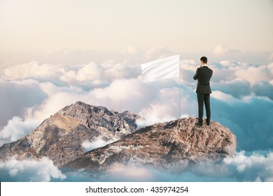 Leadership and success concept with thoughtful businessman and blank white flag on mountain top. Mock up