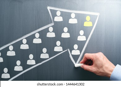Leadership and teamwork concept. Businessman drawing arrow and team on chalkboard.