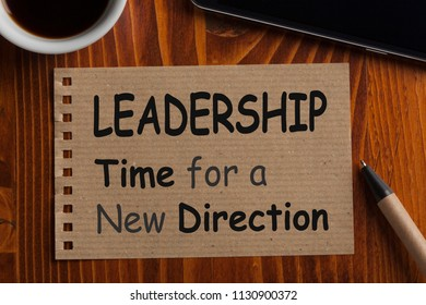 Leadership Time for a New Direction written on recycled page note with pen, smartphone and cup of coffee.