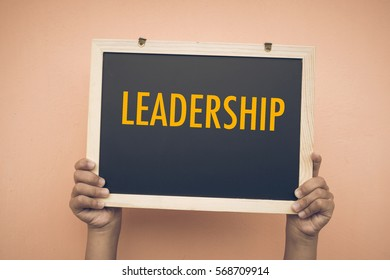 LEADERSHIP wording on chalk board with wooden background. Motivation, positive wishes, business, finance, education concept
