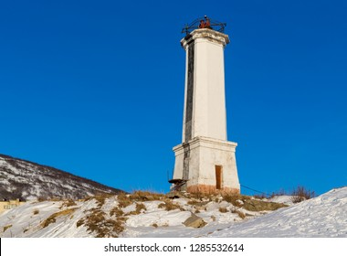 Leading beacon for marine navigation. High white lighthouse on the snow-covered shore against a blue sky. Magadan, Nagaev Bay, the Sea of Okhotsk, the Far East of Russia.