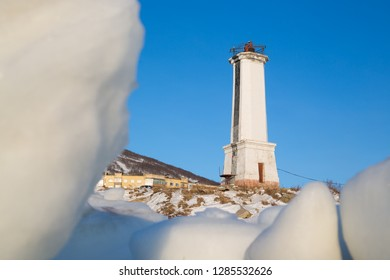 Leading beacon for marine navigation. High white lighthouse on the snow-covered shore against a blue sky. Ice in the foreground. Cold winter. Magadan, Nagaev Bay, Sea of Okhotsk, Far East of Russia.