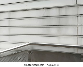 Leading line of exterior metal holder with repetition pattern of building wall