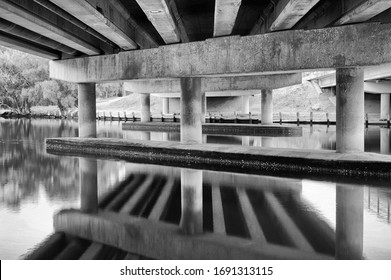 Leading lines of concrete beams, centered in the composition, with top half the underneath of the bridge, bottom half reflecting on the river, Abstract mirror image in black and white.