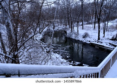 Leading lines of a snow covered bridge bring you to the over the open water of the Pike River in a Wisconsin park early in the winter season.
