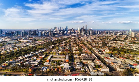 Leading streets and residential suburbs from Port Melbourne via Southbank to Melbourne city CBD against blue sky in aerial wide view.