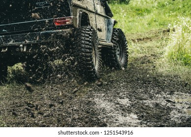 Leading up through the extreme trails. SUV or offroader on mud road. Car racing offroad. Offroad car in action. Dirty car drive on high speed. Car wheels on steppe terrain splashing with dirt.