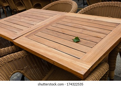 Leaf on the empty table on the terrace of open air cafe. Wooden tables and wicker armchairs.