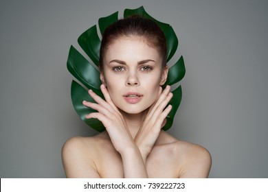 leaf of a palm tree, beautiful woman on a gray background portrait