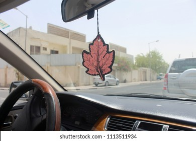 Leaf shaped decorative hanging on the rear view mirror inside the car